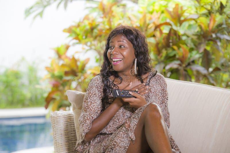 Jeune contrôleur de observation de participation de télévision de femme américaine élégante heureuse et attirante d'africain noir photographie stock
