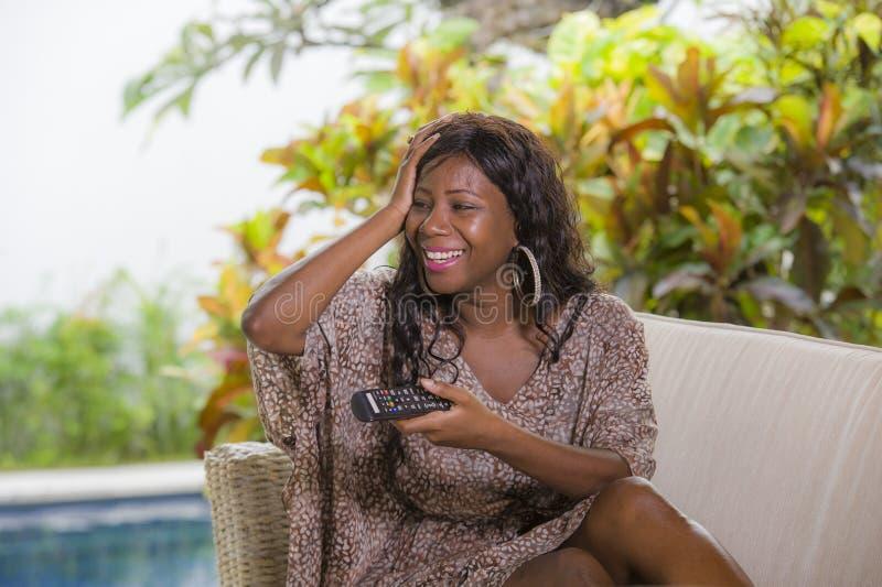 Jeune contrôleur de observation de participation de télévision de femme américaine élégante heureuse et attirante d'africain noir photos stock