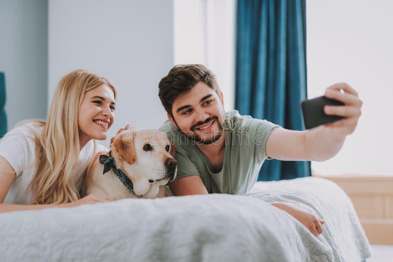 Jeune coule positif faisant le selfie avec leur chien photos libres de droits