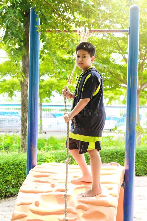 Jeune coup asiatique de garçon la barre jaune par sa main à l'exercice au terrain de jeu de porte sous le grand arbre photos stock