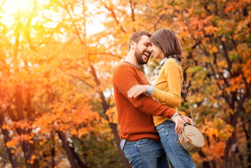 Jeune couple adoré rester et s'embrasser au parc d'automne au coucher du soleil photos libres de droits