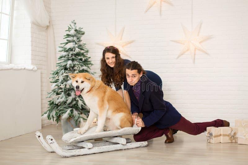 Jeune couple joyeux sur un traîneau avec un chien dans les décorations de Noël photos libres de droits