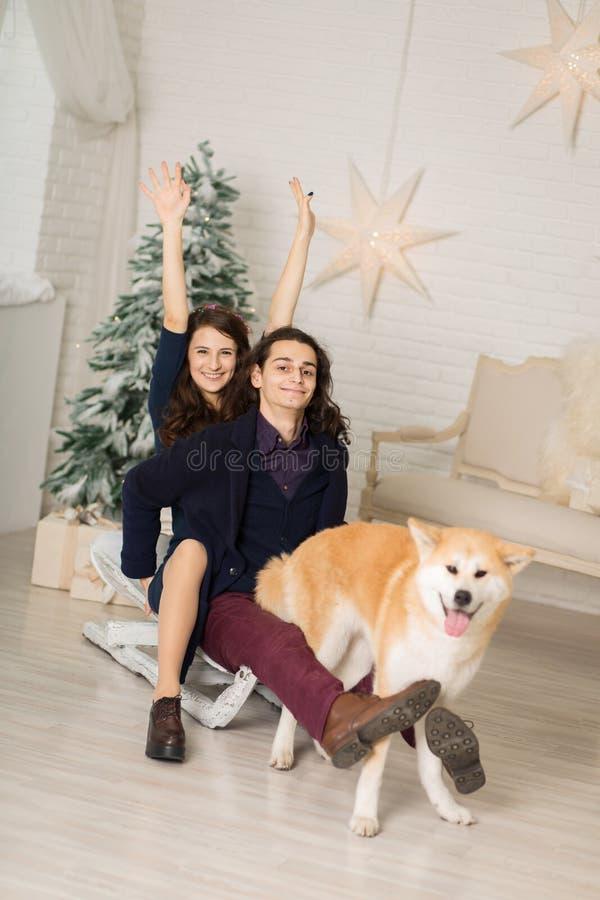Jeune couple joyeux sur un traîneau avec un chien dans les décorations de Noël photographie stock