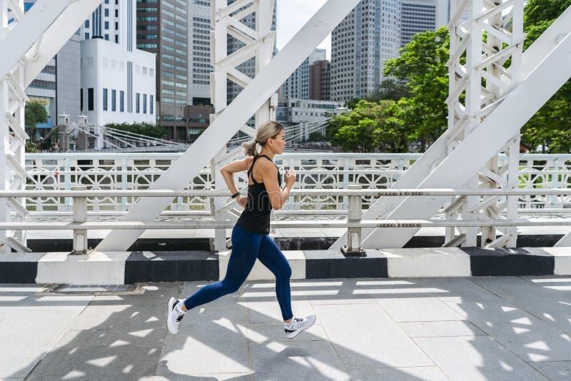 Jeune coureur asiatique de femme fonctionnant sur la route de pont de ville image stock
