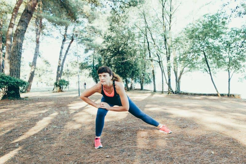 Jeune coureur de femme de forme physique étirant des jambes avant course images libres de droits
