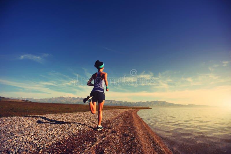 Jeune coureur de traînée de femme de forme physique fonctionnant sur le bord de la mer de lever de soleil image stock