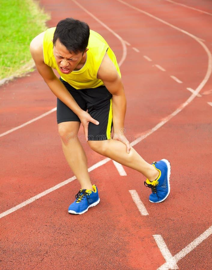 Jeune coureur masculin souffrant de la crampe de jambe sur la voie photos stock
