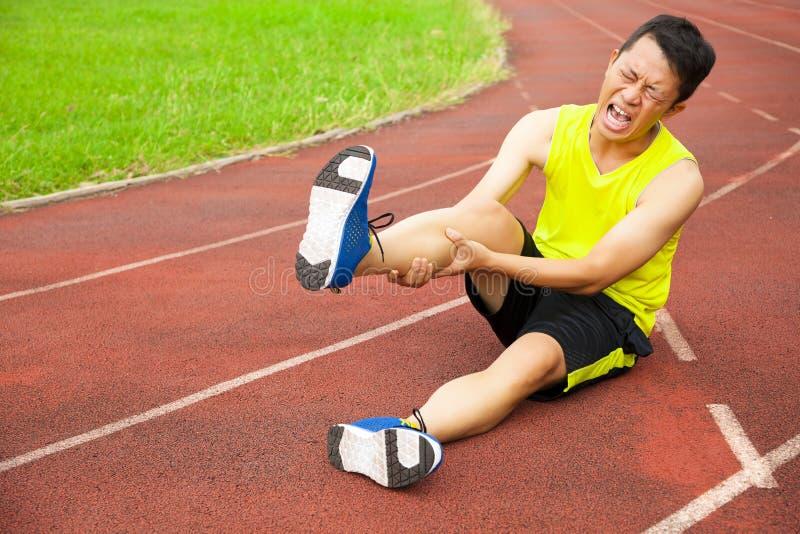 Jeune coureur masculin souffrant de la crampe de jambe sur la voie photographie stock libre de droits