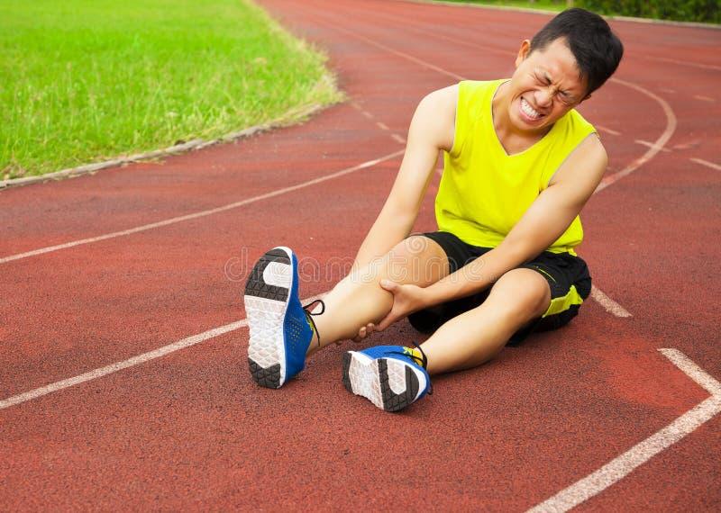 Jeune coureur masculin souffrant de la crampe de jambe sur la voie images libres de droits