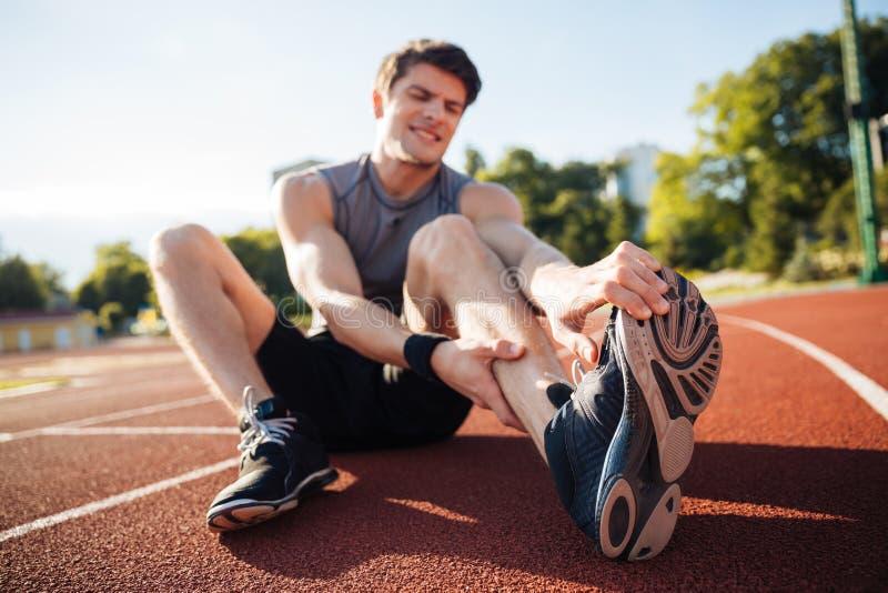 Jeune coureur masculin souffrant de la crampe de jambe sur la voie images stock