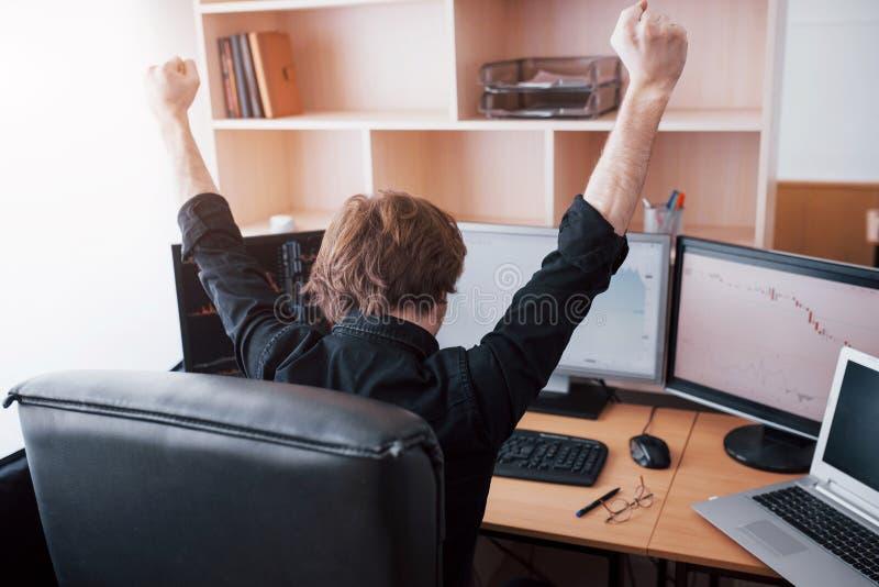 Jeune courtier d'opérateur en bourse étirant des mains sur le lieu de travail, il a réalisé la première fois le grand succès sur  images stock