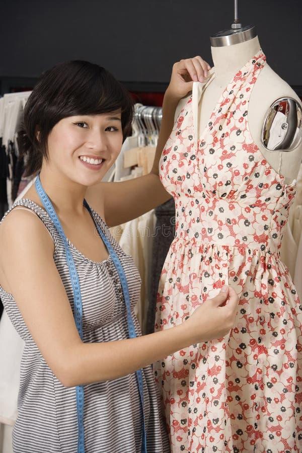 Jeune couturier ajustant la robe sur le simulacre image stock