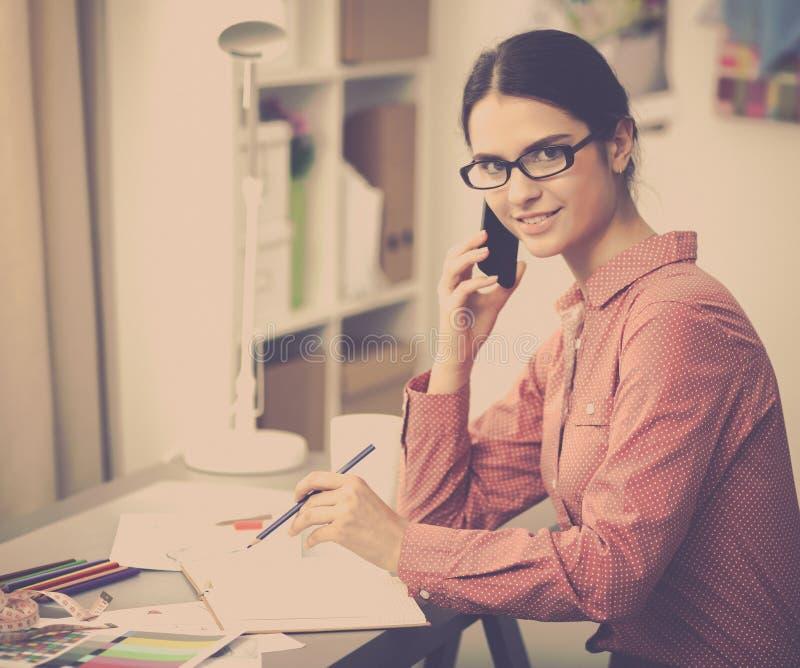 Download Jeune Couturier Féminin Attirant Travaillant Au Bureau, Dessinant Tout En Parlant Sur Le Mobile Photo stock - Image du vêtement, attrayant: 87701328