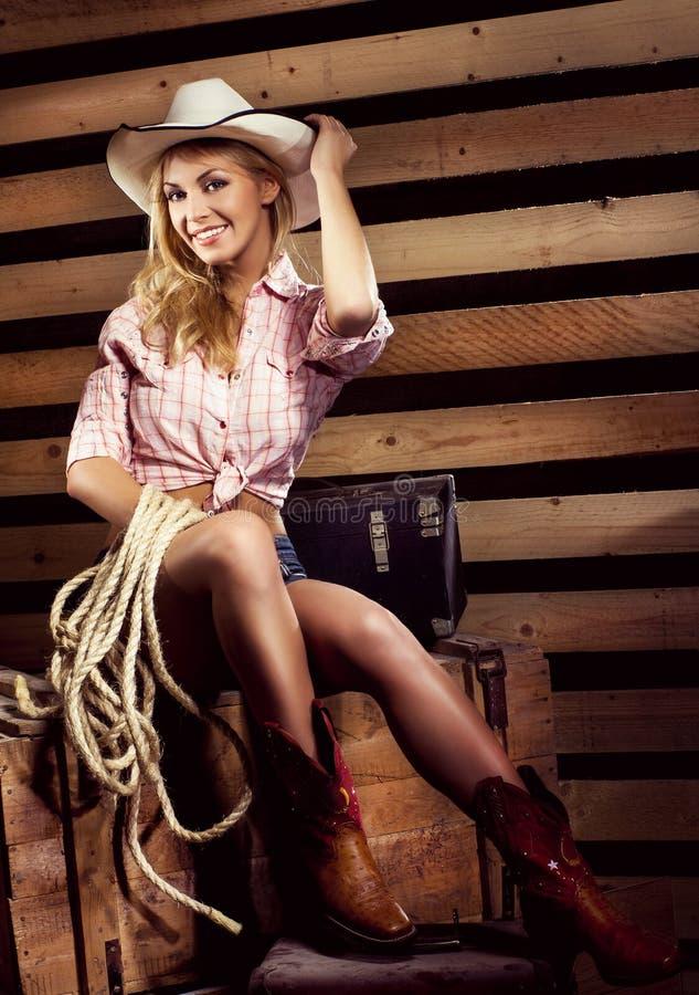 Jeune cow-girl blonde sexy avec le corps d'ajustement souriant à la ferme photographie stock