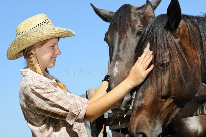Jeune cow-girl et deux chevaux photo libre de droits