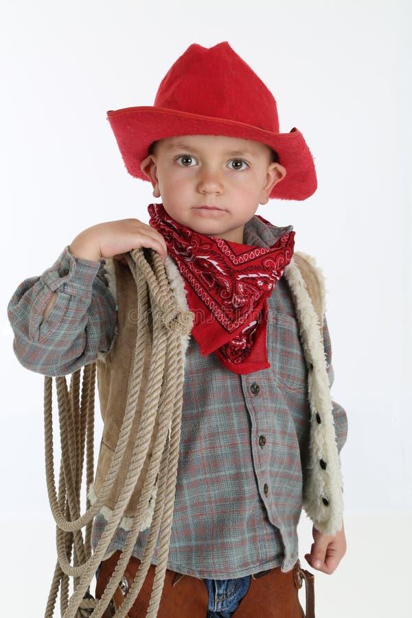 Jeune cowboy adorable utilisant un chapeau rouge et tenant une corde image stock