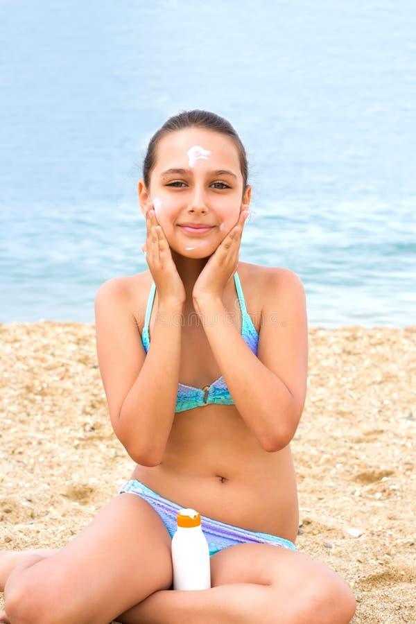 Jeune crème de protection solaire de sunblock de plage de mer d'été de fille d'adolescent images stock