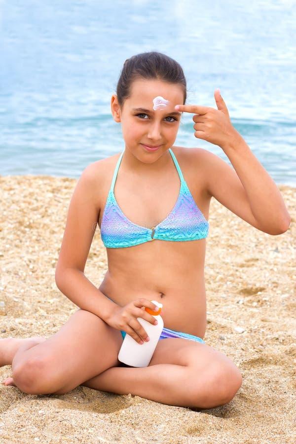 Jeune crème de protection solaire de sunblock de plage de mer d'été de fille d'adolescent image stock
