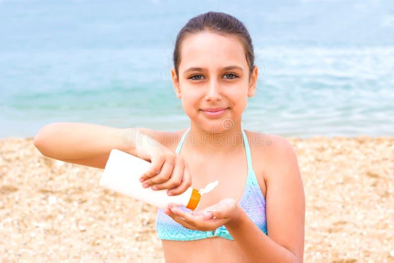 Jeune crème de protection solaire de sunblock de plage de mer d'été de fille d'adolescent image libre de droits