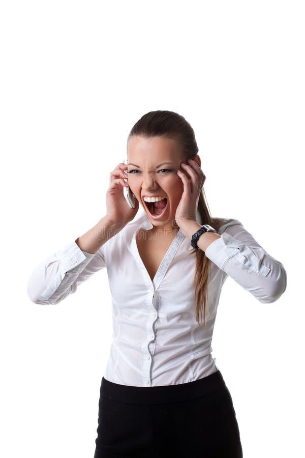 Jeune cri perçant de femme d'affaires de colère sur la cellule images stock