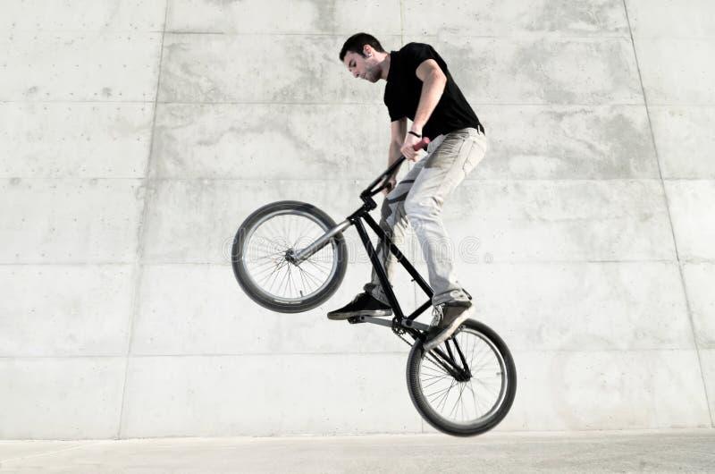 Jeune curseur de bicyclette de BMX image stock