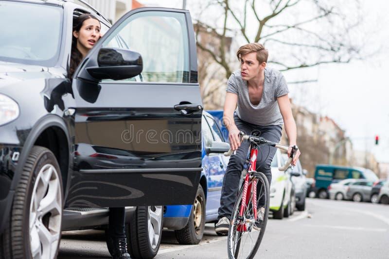 Jeune cycliste criant tout en faisant un écart pour éviter la collision dangereuse photos stock
