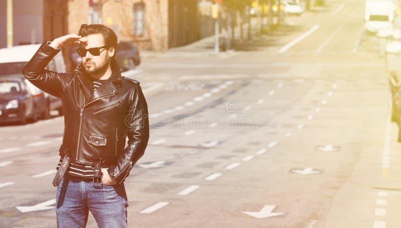 Jeune cycliste dans une veste en cuir noire et des lunettes de soleil regardant loin sur la route brouillée sur le fond horizonta photo stock