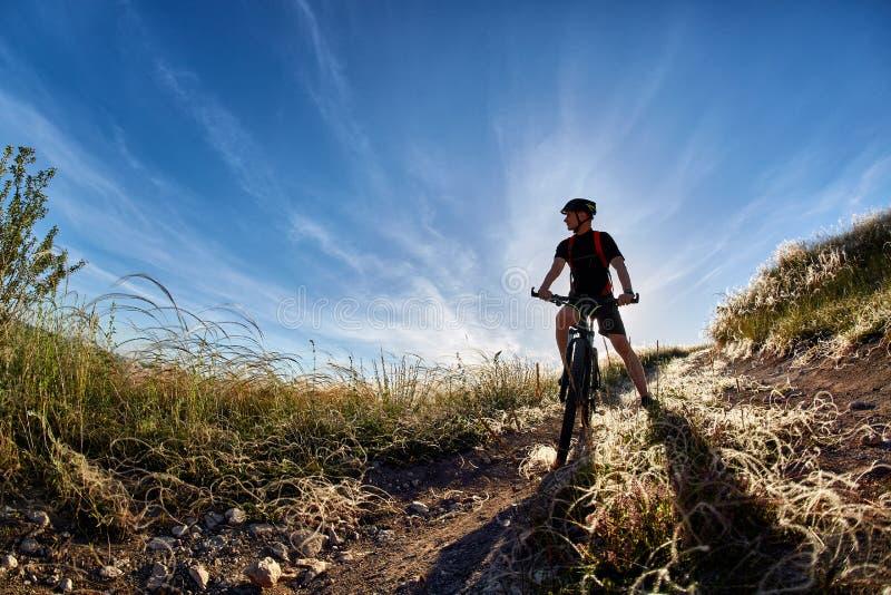 Jeune cycliste de montagne d'équitation de cycliste contre le beau coucher du soleil dans la campagne image stock