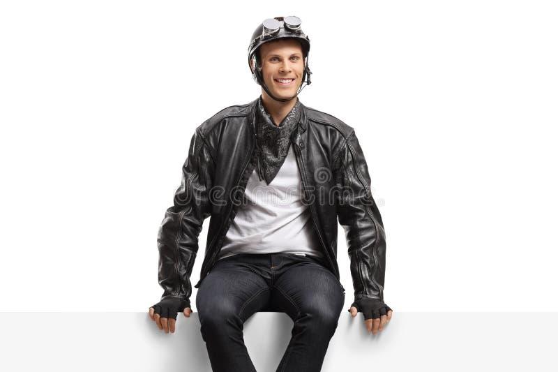 Jeune cycliste de type s'asseyant sur un panneau et regardant la caméra images stock