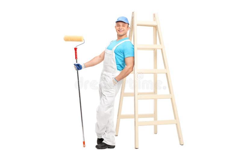 Jeune décorateur masculin tenant un rouleau de peinture photographie stock