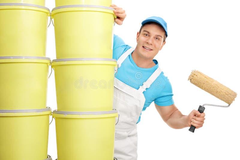Jeune décorateur masculin tenant un rouleau de peinture images stock