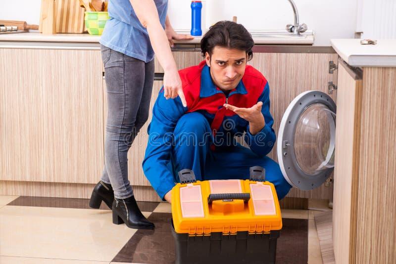 Jeune dépanneur masculin réparant la machine à laver images stock