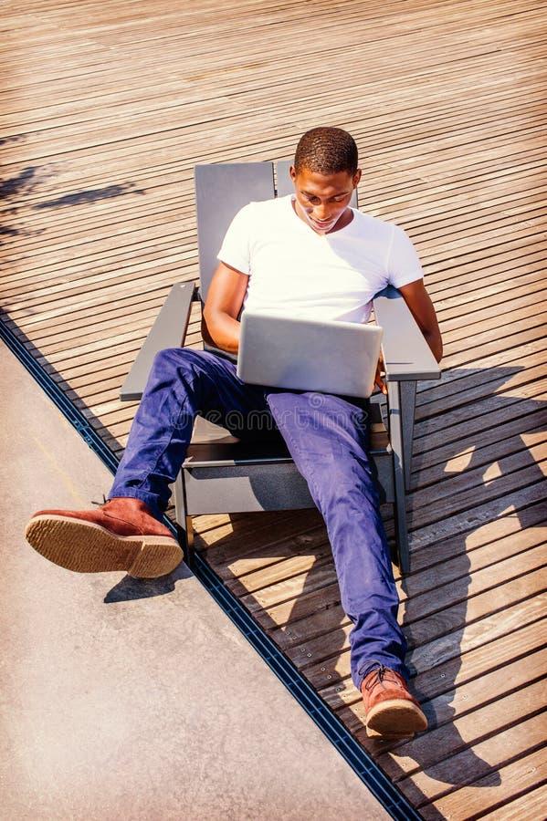 Jeune déplacement d'homme d'Afro-américain, travaillant sur l'ordinateur portable photos stock