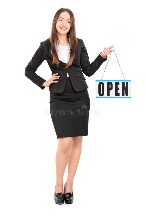 Jeune détaillant féminin tenant un signe ouvert photo stock