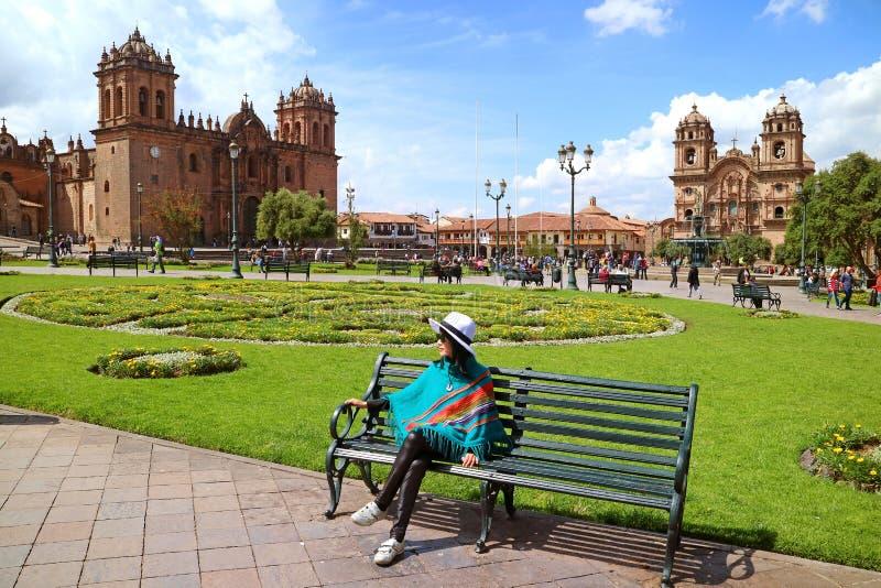 Jeune détente femelle sur un banc chez Plaza de Armas avec la cathédrale de Cusco et Iglesia de la Compania De Jésus à l'arrière- photos stock