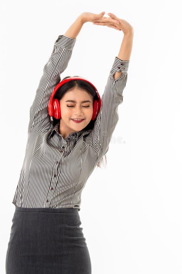 Jeune dame asiatique utilisant les écouteurs rouges étirant ses bras au-dessus de sa tête images stock