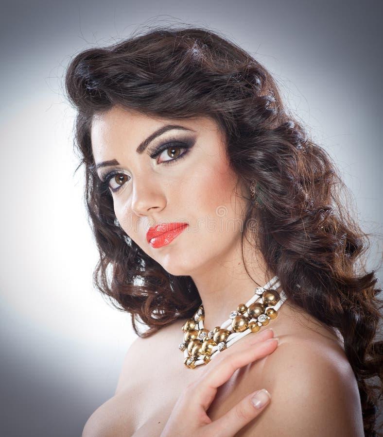 Jeune dame attirante de brune avec le maquillage et la belle coiffure posant sur le fond gris dans le studio images stock