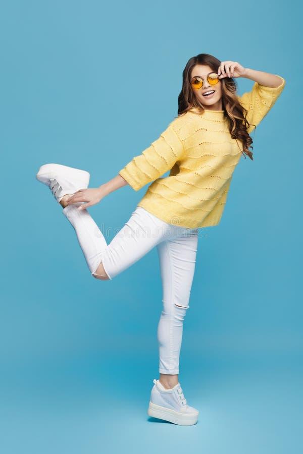 Jeune dame attirante posant sur le fond bleu Jolis danse de fille et amusement de avoir Vol de cheveu photo stock