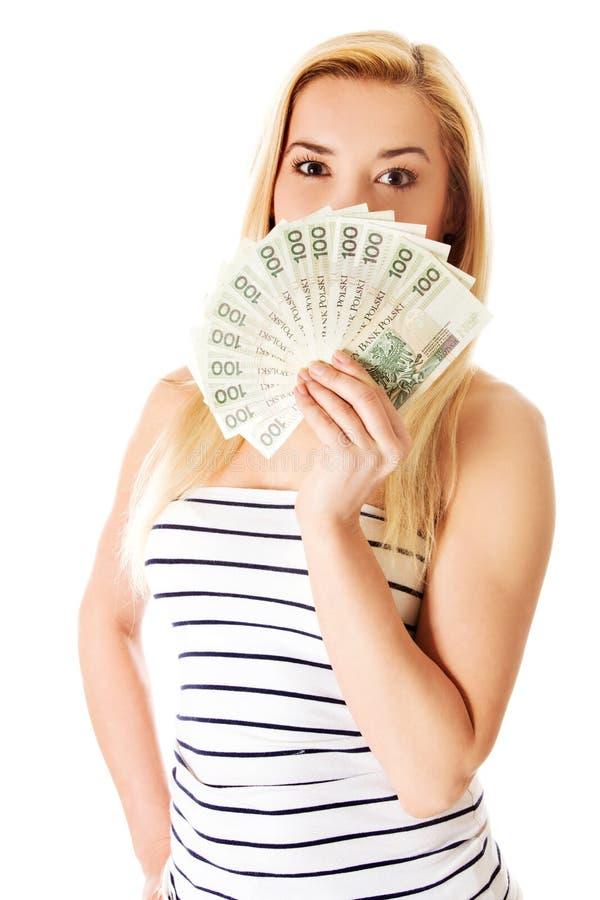 Jeune dame attirante tenant l'argent liquide et le sourire heureux au-dessus du fond blanc images libres de droits
