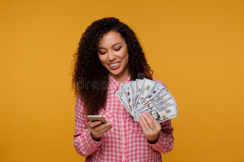 Jeune dame au-dessus de fond bleu Regard de l'affichage d'apparence d'appareil-photo du téléphone portable tenant l'argent photo stock