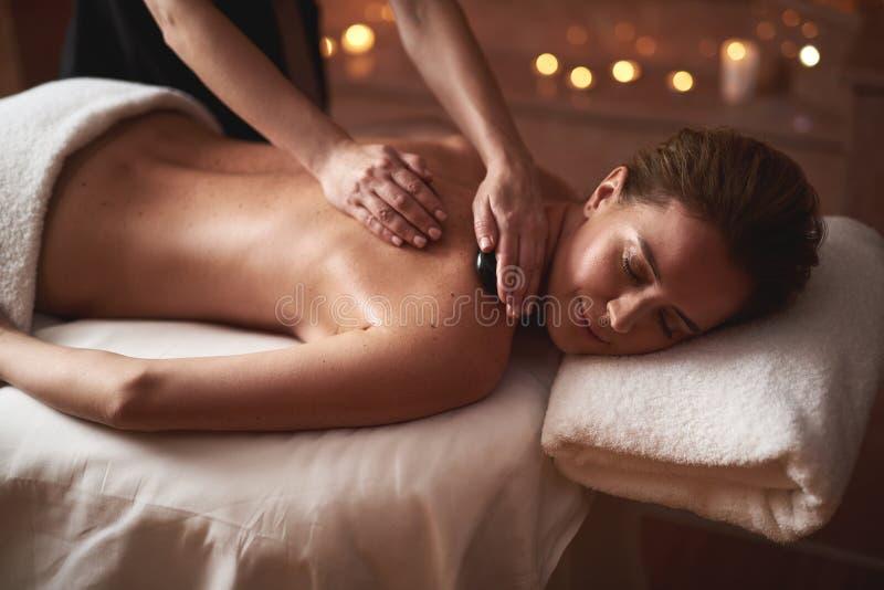 Jeune dame ayant le massage avec les pierres chaudes photo stock