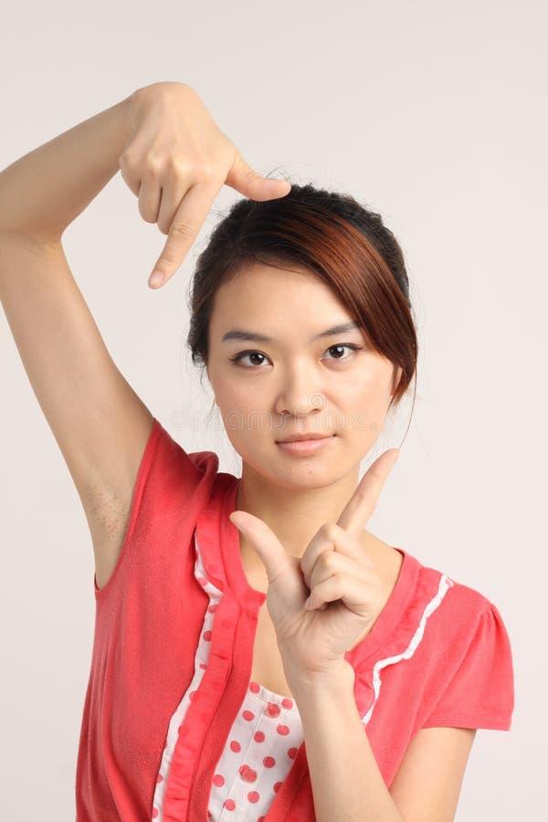 Jeune dame chinoise dans la pose occasionnelle d'appareil-photo-clic photo libre de droits