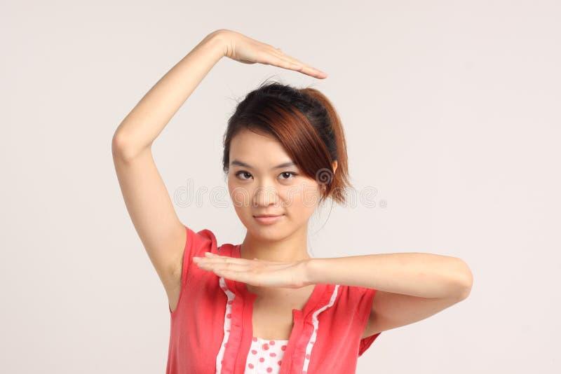 Jeune dame chinoise dans la pose occasionnelle principale et d'épaule images stock