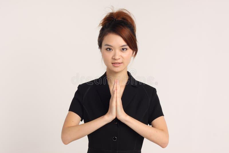 Jeune dame chinoise dans le vêtement formel avec la pose de Namaste photos libres de droits