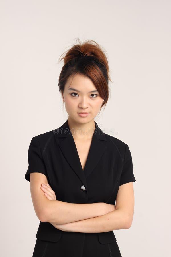 Jeune dame chinoise dans le vêtement formel avec les mains croisées images stock