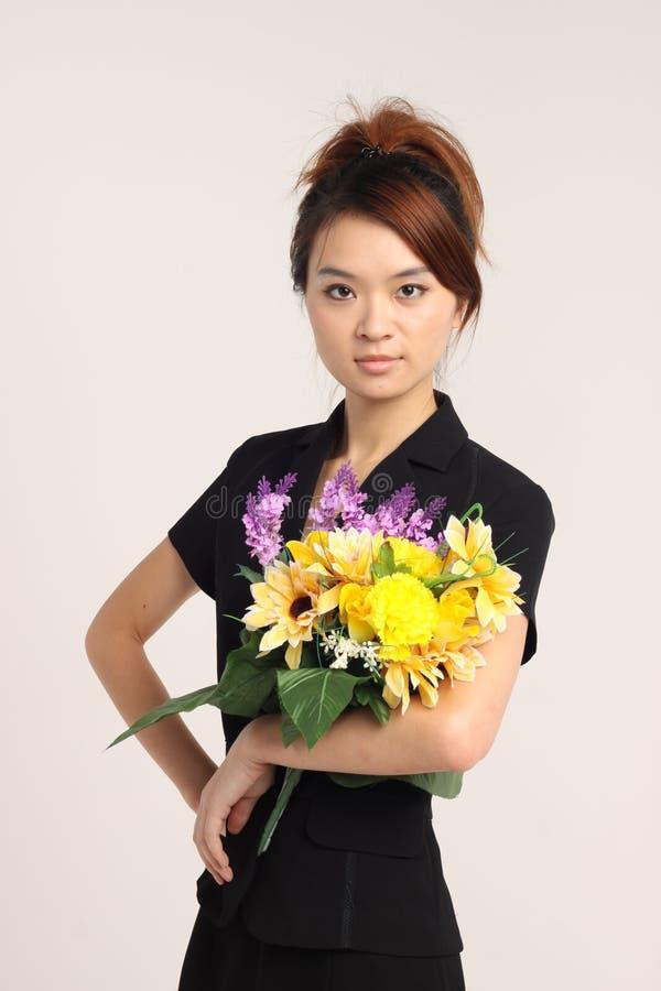 Jeune dame chinoise dans le vêtement formel tenant des fleurs image libre de droits