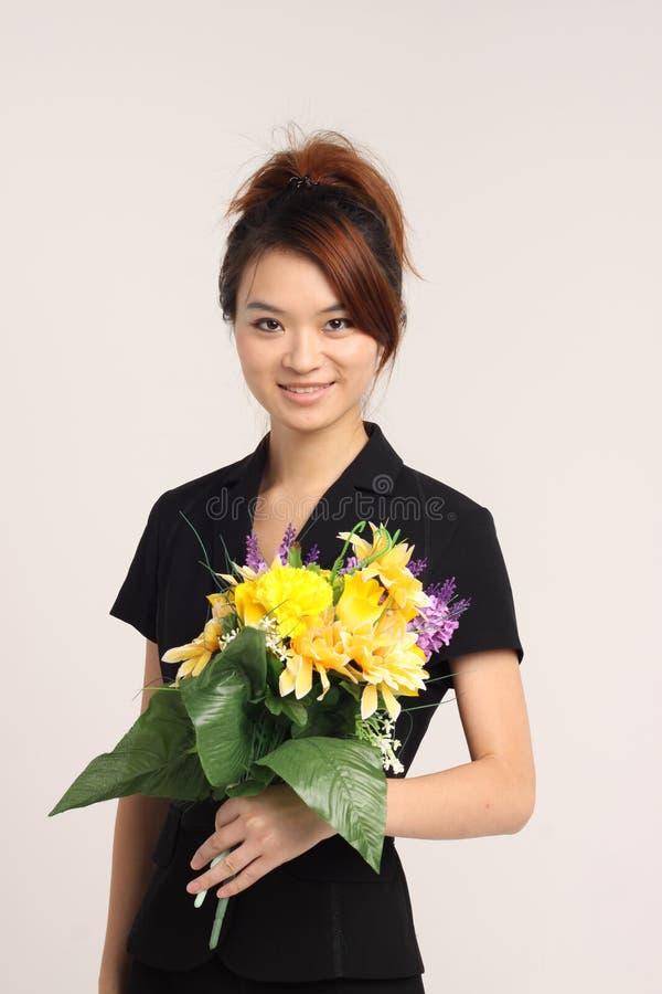 Jeune dame chinoise dans le vêtement formel tenant des fleurs photographie stock