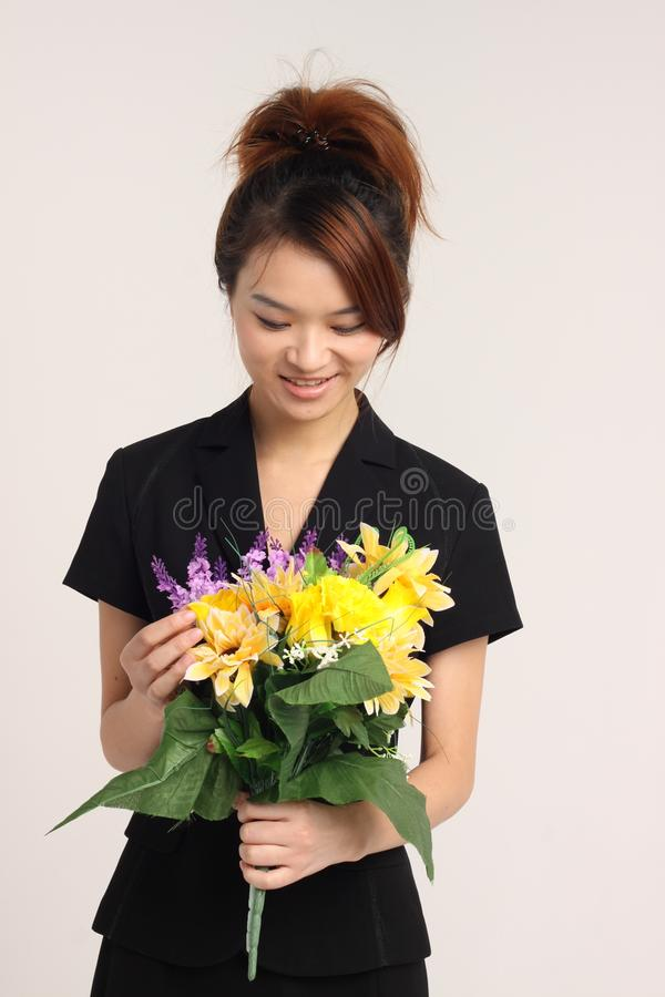 Jeune dame chinoise dans le vêtement formel tenant des fleurs images libres de droits