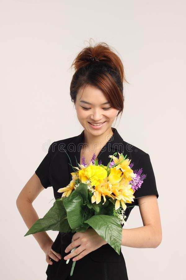 Jeune dame chinoise dans le vêtement formel tenant des fleurs et le sourire image libre de droits