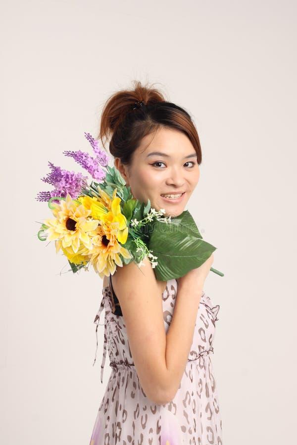Jeune dame chinoise dans le vêtement occasionnel avec un groupe de fleurs images stock